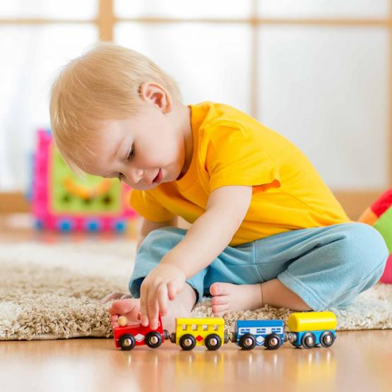 Child playing with toy train on the floor